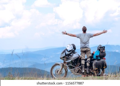 Motorcyclist man stands with his arms outstretched Adventure Motorbike on the top of the mountain. Motorcycle trip. off road Traveling, Lifestyle Travel vacations sport outdoor concept.