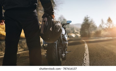 Motorcyclist with motorcycle on a road