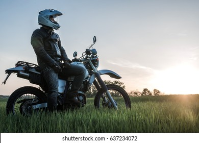 Motorcyclist on green grass off road, enduro, extreme sport, active lifestyle, adventure touring concept, enduro outdoor