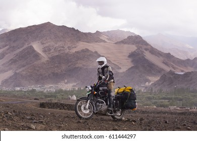 Motorcyclist on a mountainous road, cold overcast weather. Extreme sport, active lifestyle, adventure touring concept. High mountains, dirt roads.
