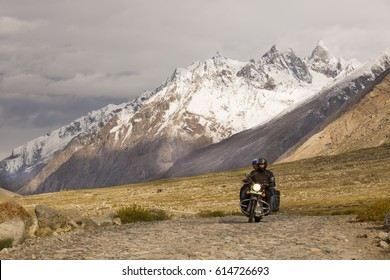 Motorcyclist on a mountainous road, cold overcast weather, bright sun. Extreme sport, active lifestyle, adventure touring concept. Snowy high mountains, dirt roads.
