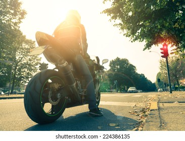Motorcyclist on the road - Racing motorbike stops at traffic lights at sunset