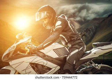 Motorcyclist on sport bike stands on the edge of the mountains in the background of a bright sunset. motorcyclist in helmet on motorcycle against mountains and sun