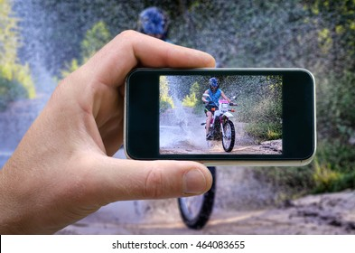 motorcyclist passes at high speed through the water stream. photo on the phone, the person photographed on a smartphone from the