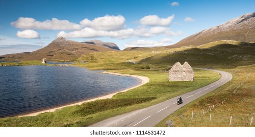 A motorcyclist passes the ruins of Calda House and Ardvreck Castle on Loch Assynt, with Quinag mountain behind, on the A837, part of the North Coast 500 touring route in the remote Scottish Highlands.