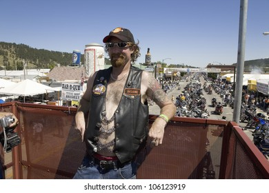 Motorcyclist posing on Main Street with overview of 67th Annual Sturgis Motorcycle Rally, Sturgis, South Dakota, August 6-12, 2007