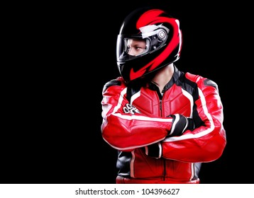 Motorcyclist in red equipment and helmet on black background looking to the copy space area