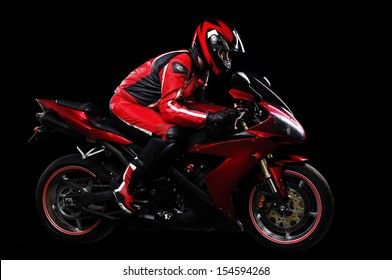 Motorcyclist in red equipment and helmet on black background side view full length