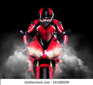 Motorcyclist in red equipment and helmet riding motorbike with headlights on  over black background