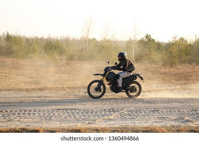 Motorcyclist rides a dirt bike. Biker on the dusty road.
