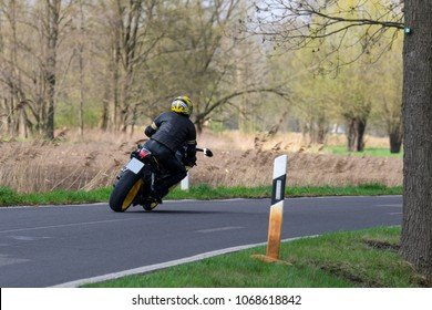 Motorcyclist rides very sporty around a bend on a country road
