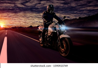 motorcyclist riding his motorbike on a country road in the early morning while sunrise. the orange backlight draws a nice silhouette on his body and bike. copy space on left for your own creativity