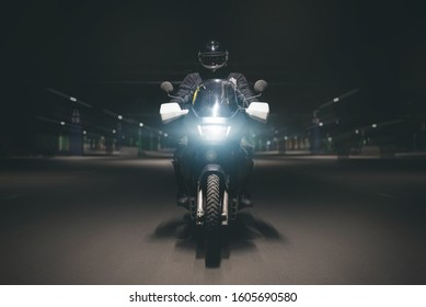 Motorcyclist is riding his motorbike on night parking road.