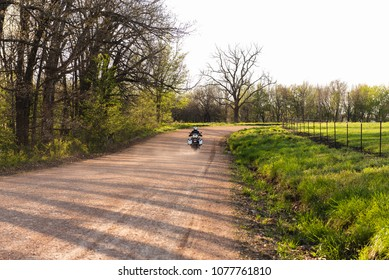 A motorcyclist riding a motorcycle on a country dirt road in the late afternoon.