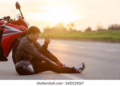 Motorcyclist sitting on the road beside his motorcycle and drinking an alcohol or beer. Safe ride concept