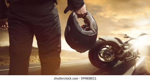 Motorcyclist standing with motorcycle on a road