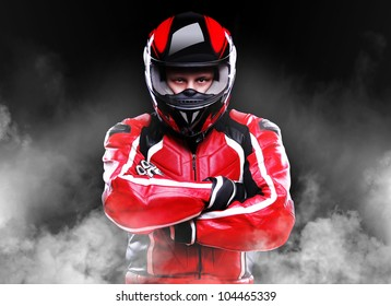 Motorcyclist standing in smoke on black background