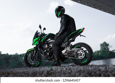 Motorcyclist stop under the bridge over the road waiting for rain to stop