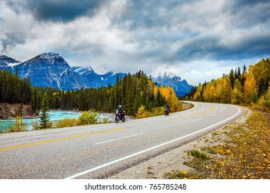 """Motorcyclists driving on the road. The concept of active tourism. The astonishing nature of the Rockies of Canada. The road 93 """"Icefields Parkway"""" passes among the snow-capped mountains"""