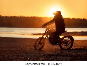 Motorcyclist's silhouette on electric motorbike in sunset light and dust