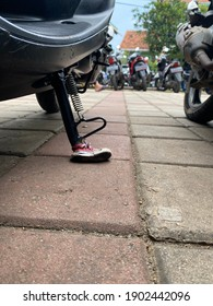 Motorcylce kickstand, using mini sneakers. In Indonesia