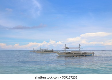 Motor-driven boats floating near the shore of Panglao Island, Philippines. These boats are used for island hopping and dolphin watching.
