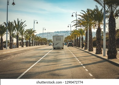 Motorhome arriving in summer paradise in street full of coconut palms and palm trees in beach town. Auto Caravan on the street seen from behind traveling from summer holidays