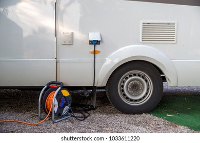 Motorhome with connected electric cable on a campground