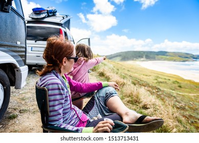 Motorhome RV or campervan is parked on a beach. Family on vacation is sitting outsides on camping chairs and table having dinner, with amazing view of the beach and ocean. Atlantic beach - Spain.