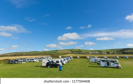 Motorhomes and campervans parked on a camping site in beautiful field in summer with blue sky