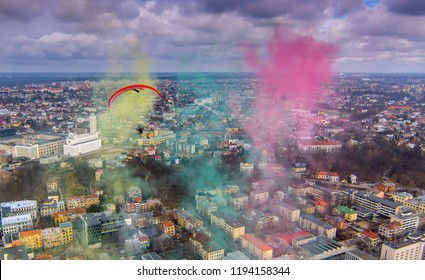 motorised paraglider flying thru the colored smoke Yellow green red . Kaunas, Lithuania. Independence day.