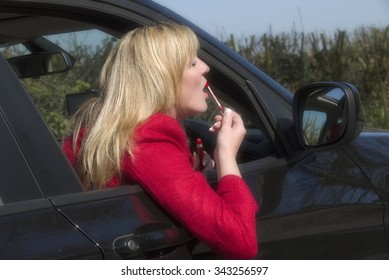 Motorist applying lip gloss using a car driving mirror