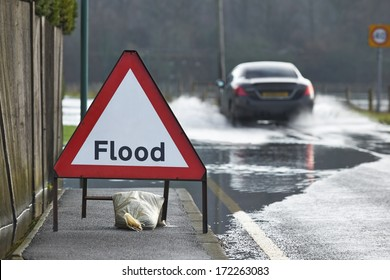 Motorist driving through flood waters with warning sign in foreground