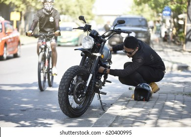 A motorist having problems with his motorcycle during a trip. Serious young man repairing his motorcycle during trip.