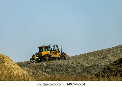 Motorized bulldozer raking rubble piles to uphill. Road building industry.