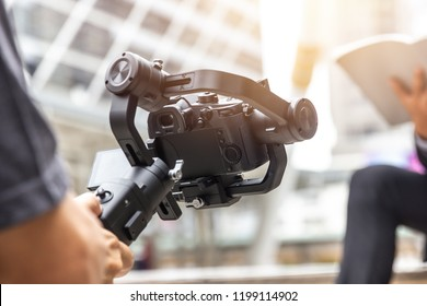 motorized gimbal, videographer using dslr camera anti shake tool  for  stabilizer record video scene.