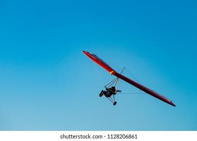 Motorized glider in blue sky