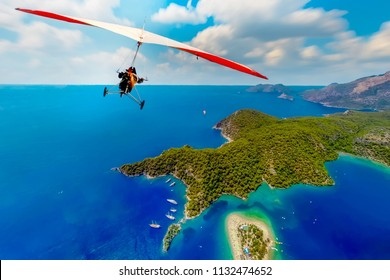 The motorized hang glider in the blue sky  and Blue Lagoon in Oludeniz, Turkey. Extreme sport. Landscape