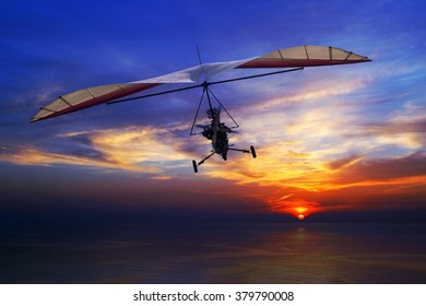 The motorized hang glider in the sunset above sea