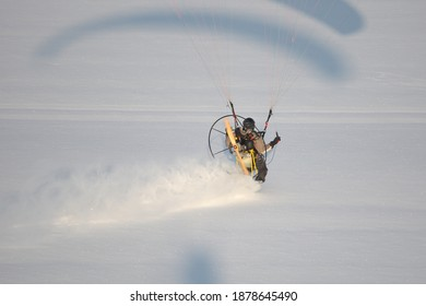 Parapente motorisée vue du ciel volant en hiver dans un paysage blanc et laissant une piste dans la neige