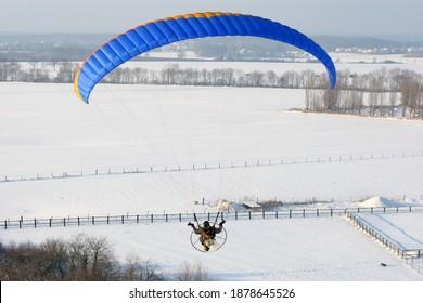 Parapente motorisée vue du ciel survolant les champs en hiver, enneigé
