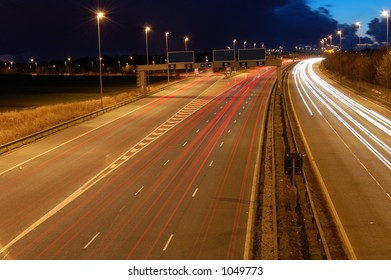 Motorway just as it goes dark with traffic travelling at speed in both directions.With blank signs for your text.