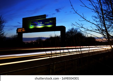 Motorway sign at dusk, during essential travel hours due to the coronavirus outbreak.