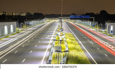 Motorway with tunnel at night with blurred car lights by long exposure