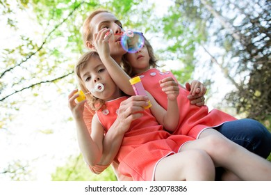 Motzher with twin girls blowing soap bubbles