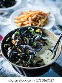 Moules Frites – clams with french fries. Cooked fries in a black pan with french fries in background.