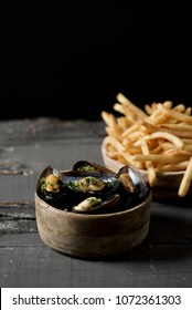 moules-frites, mussels and fries typical of Belgium, on a rustic wooden table, against a black background, with some blank space on top