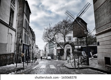 Moulin de la Galette in Montmartre (Paris, France) with melting snow on the side of the street