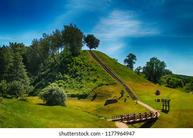 Mound in Lithuania with green grass and trees background, road to mountain with bridge,