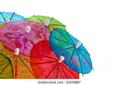 A mound of multi-colored cocktail umbrellas isolated on white.